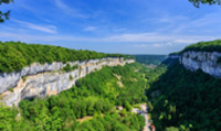 Travel to Baume-les-Messieurs which is surrounded by steep wooded slopes rising to high cliffs.