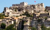 Travel to the Village of Baux-de-Provence, situated atop a rocky outcrop and crowned with a ruined castle.